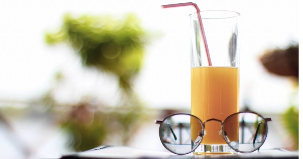 Eyeglasses and a refreshing orange juice resting on a table outdoors